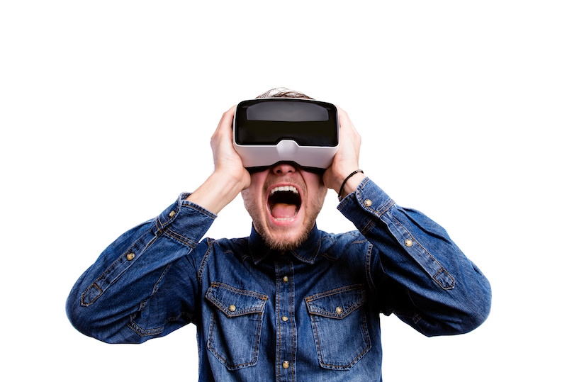 Hipster man in denim shirt wearing virtual reality goggles. Studio shot on white background
